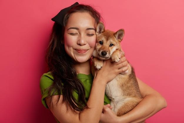 女性と犬の親友はカメラで一緒にポーズをとり、愛を抱き、友好的な関係を持っています。