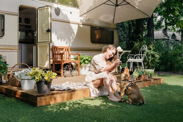 Женщина и собака в кемпинге и путешествуют на автофургоне