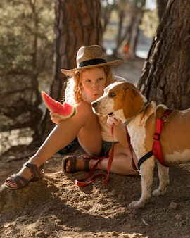 Женщина и собака едят ломтик арбуза