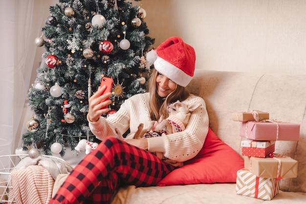 Женщина и собака в свитере с удовольствием принимает селфи-портрет