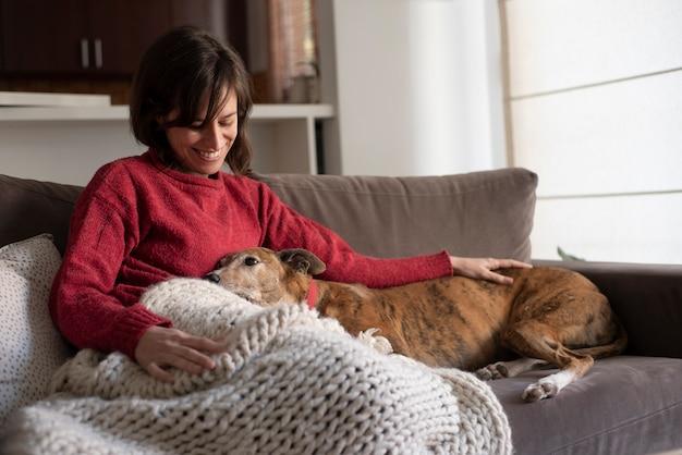 Женщина и собака, отдыхая на диване