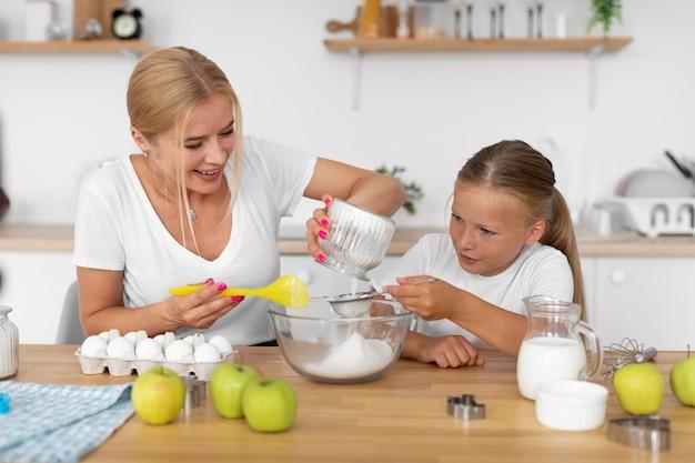 ミディアムショットを調理する女性と少女