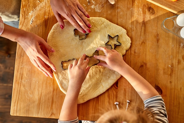 Женщина и девушка руки резают тесто формочками для печенья на кухне