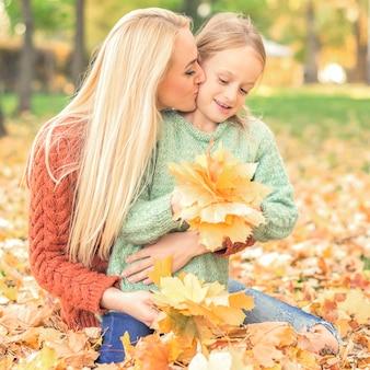 秋の黄色の葉を保持している女性と少女