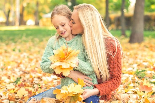 Женщина и девочка, держащая осенние желтые листья