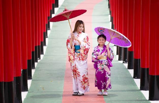 日本庭園の神社に傘をさして歩いている着物の女性と少女。