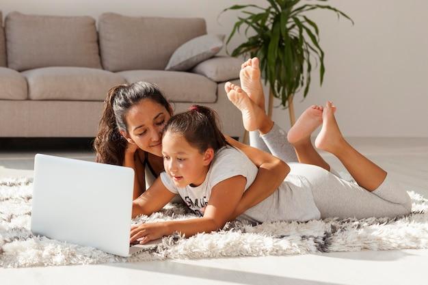 女性と少女がカーペットの上に敷設