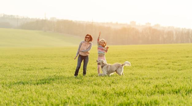 Женщина и девушка играют с собакой
