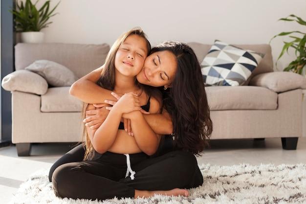 女性とカーペットの上に座っている女の子