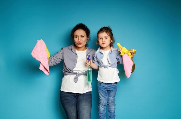 Женщина и девушка с чистящими средствами в руках позирует впереди, выражая недовольство уборкой