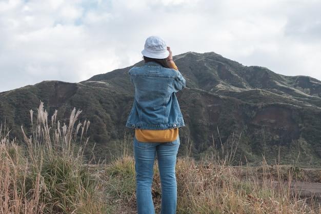 Женщина и зеленый пейзаж с горы асо фон, кусасенри, кумамото, кюсю