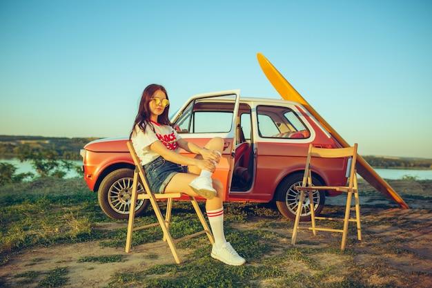 자동차로 여자와 행복한 여행. 강 근처에서 도로 여행을하는 동안 차에 앉아 웃는 소녀