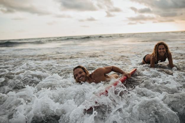 海でサーフィンする女性と彼女のボーイフレンド