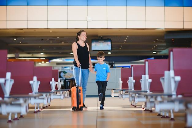 Женщина и ее ребенок проезжают через терминал аэропорта