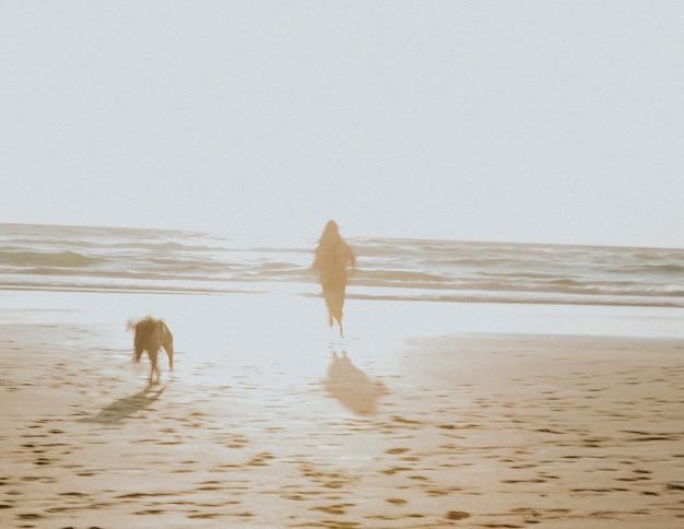 Женщина и ее собака играют на пляже