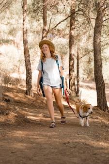 Женщина и ее собака гуляют в лесу