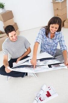 여자와 그녀의 남편이 그들의 집 계획을보고