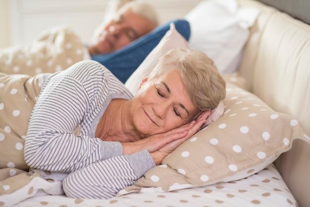 快適に眠る女性と夫
