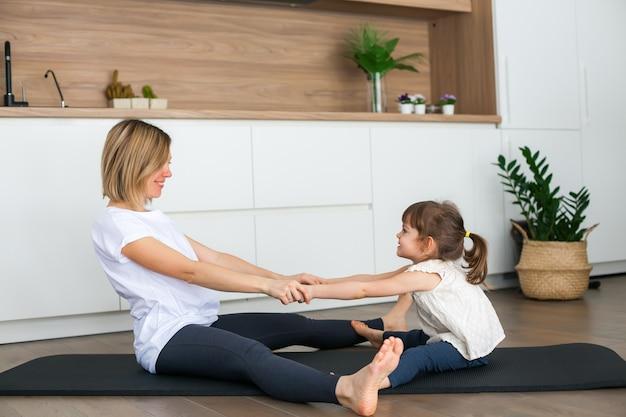 Женщина и ее маленькая дочь растягиваются, тренируясь вместе дома