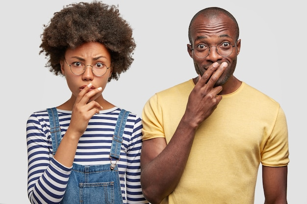 女性と彼女の男性の友人はカメラを注意深く見て、口に指を持っています