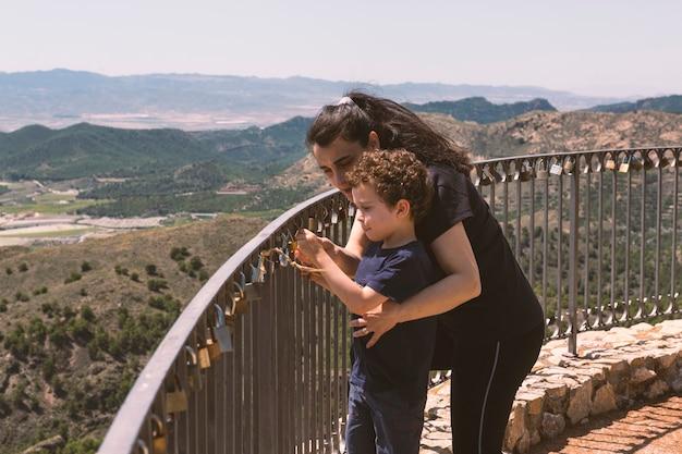 ガゼボの手すりにカップルが置いた南京錠を観察している女性と彼女の幼い息子
