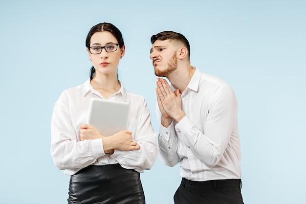 여자와 그의 비서 사무실이나 스튜디오에 서. 그의 동료에 게 구걸하는 사업가. 사무실 관계 개념, 인간의 감정