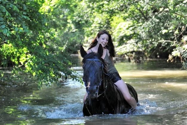 女性と川の馬