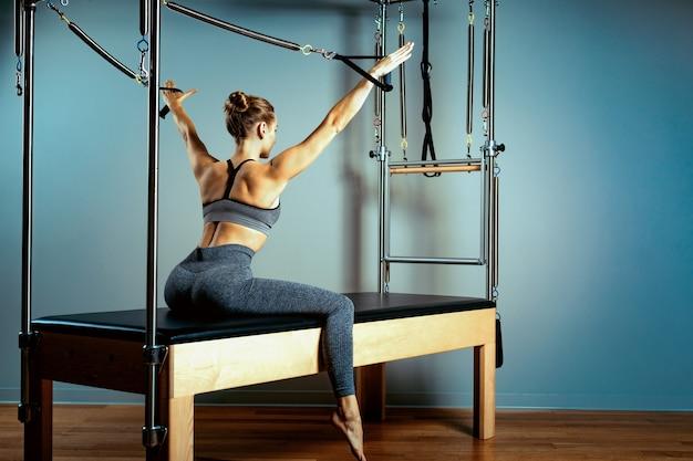 筋骨格系の治療のためのシミュレーター改質装置で演習を行う女性とインストラクター。