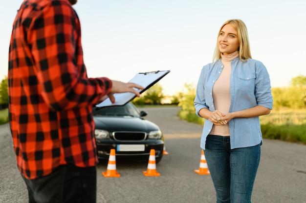Женщина и инструктор с контрольным списком на дороге, урок в автошколе. мужчина учит леди водить автомобиль. образование водительского удостоверения