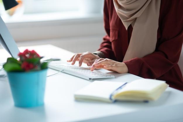 女性とキーボード。素敵な家の植物とテーブルに座っている間、キーボードで入力する女性をクローズアップ