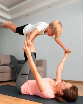 Женщина и ребенок занимаются йогой в полный рост