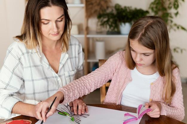 一緒に絵を描く女性と子供