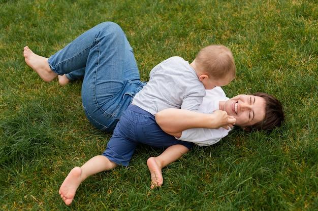 잔디 풀 샷에서 노는 여자와 아이