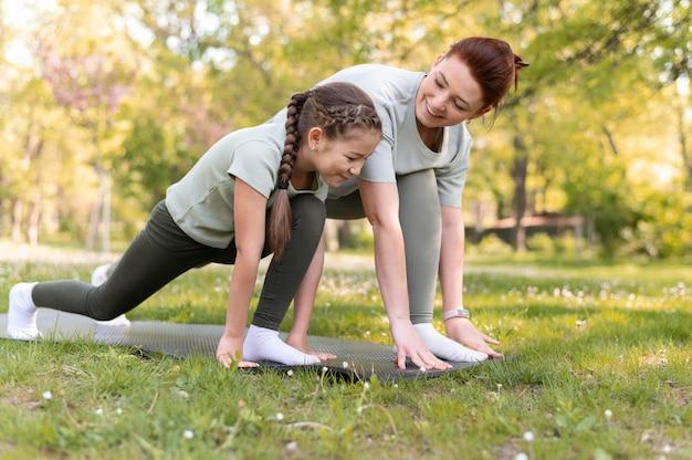 Женщина и ребенок тренируются вместе, полный кадр