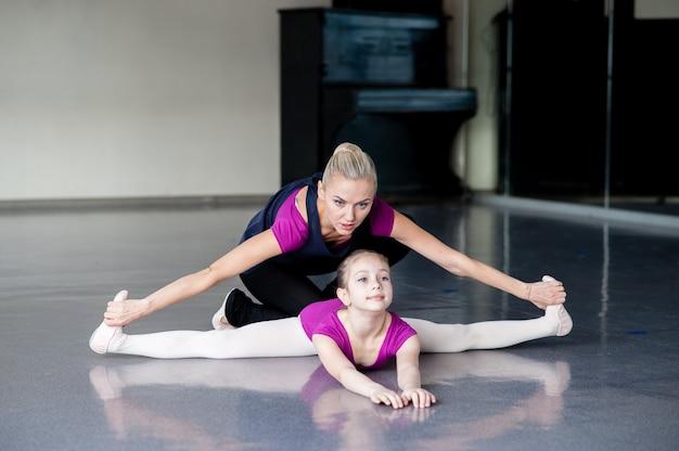 Женщина и маленькая девочка тренируются вместе