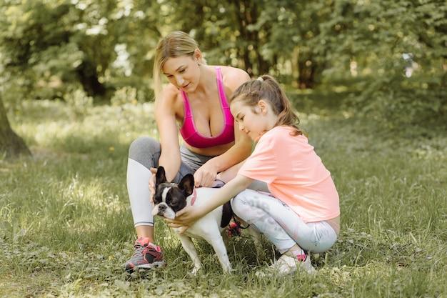 女性と少女は公園で犬と一緒に散歩に行きます