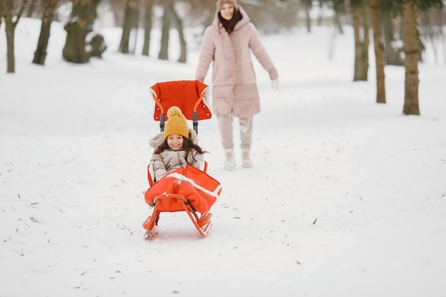 여자와 썰매와 함께 공원에서 어린 소녀