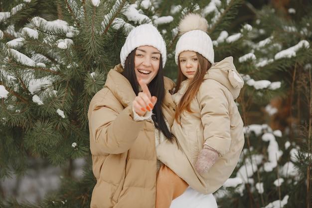 雪に覆われた公園の女性と少女