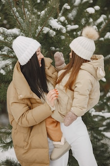여자와 눈 덮인 공원에서 어린 소녀