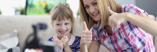 Женщина и маленькая девочка показывает палец вверх перед камерой дома