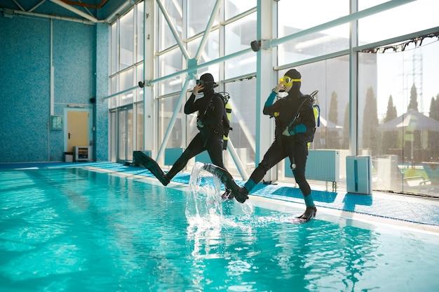 스쿠버 장비를 입은 여성과 남성 다이브마스터, 다이빙 학교 과정. 사람들에게 수중 수영을 가르치고, 배경에 실내 수영장 내부