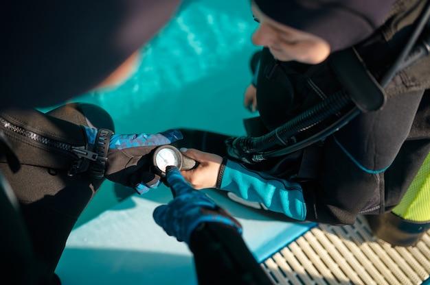 스쿠버 장비를 입은 여성과 남성 강사, 다이빙 학교 수업. 사람들에게 수중 수영을 가르치고, 배경에 실내 수영장 내부