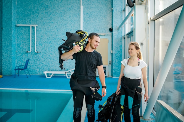 Женщина и мужчина-инструктор в костюмах, школа подводного плавания
