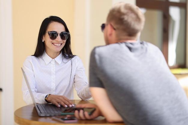 Женщина и мужчина разговаривают за столом рядом с ноутбуком