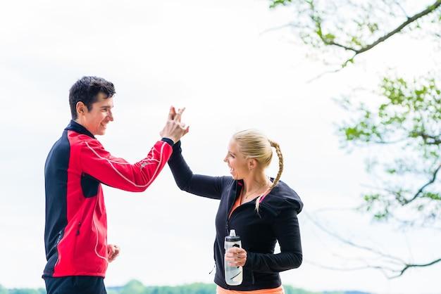 Женщина и мужчина в перерыве от бега, давая друг другу высокую пятерку
