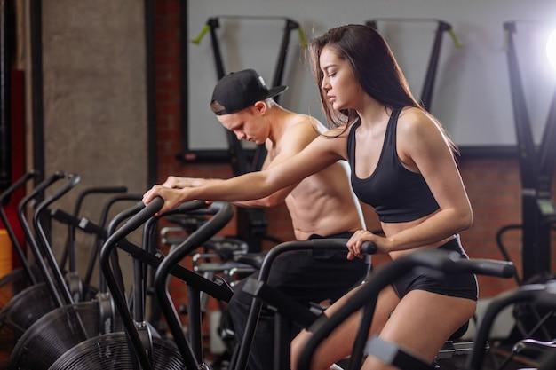 女と男のジムで自転車に乗って、カーディオトレーニングサイクリングバイクをやって足を行使