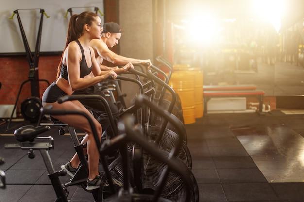 Женщина и мужчина, езда на велосипеде в тренажерном зале, упражнения ноги делают кардио тренировки велотренажеры