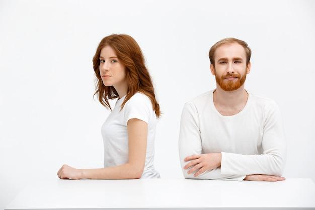 女と男の両方の赤毛がテーブルに座る