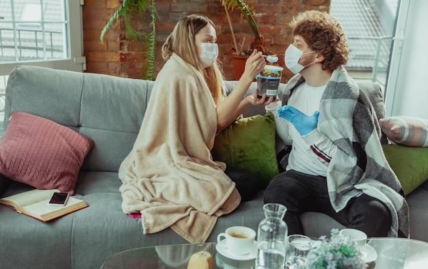 열, 두통, 기침과 같은 코로나바이러스 호흡기 증상으로 집에서 격리된 보호 마스크와 장갑을 끼고 있는 여성과 남성 부부. 건강 관리, 의학, 검역, 치료 개념.