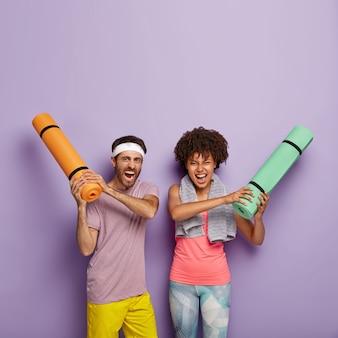 女性と男性は巻き上げられたカレマットを握り、大声で叫び、カジュアルな服を着て、ヨガのトレーニングを受けます
